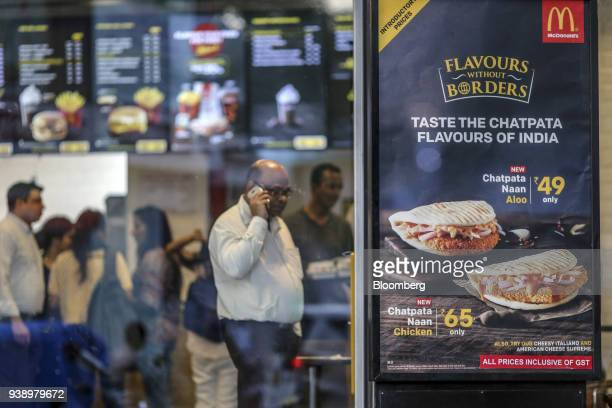 Menu items are displayed in the window of a McDonald's Corp restaurant operated by Hardcastle Restaurants Pvt in Mumbai India on Tuesday March 20...