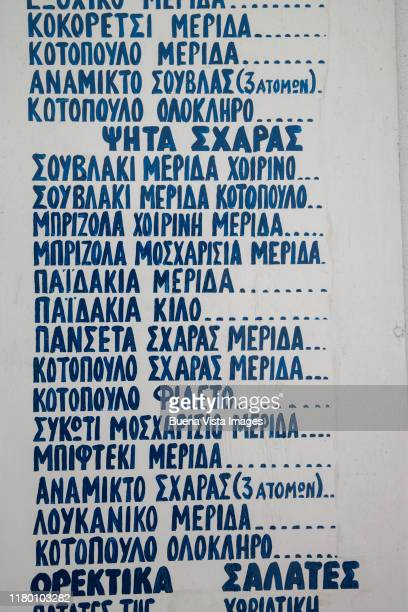 menu on the wall of a greek restaurant - scrittura non occidentale foto e immagini stock