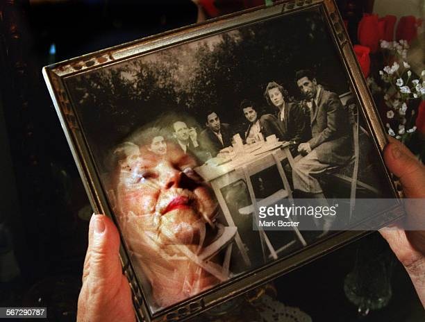 MEOpdykeReflectH060898MB–––The face of Irene Gut Opdyke is reflected in the glass of picture frame as she looked at a group photo of some of the...