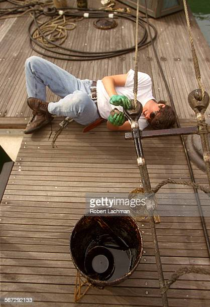 MEPilgrimDockRDL Volunteer Janet Cherpes applies tar to a rope ladder on the dock next to the Pilgrim tall ship at the Orange County Marine Institute...