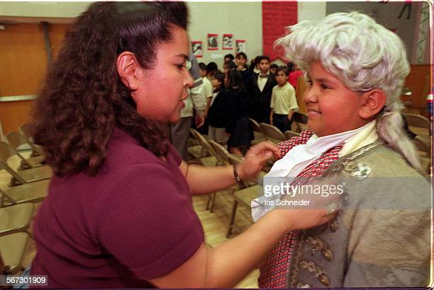 MEPresidents20214ISIngrid Vides adjusts the collar on her son Henry's waistcoat before his performance for President's Day Assembly at Betty...