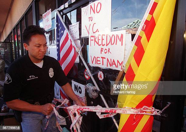 MEProtestCopRH––0211998––Westminster police officer Tim Vu takes down tape that was put up by protesters in front of Truong Van Tran's infamous video...