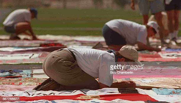MEQuilt#309–21BC/FGroup of volunteers tie together sections of the Aids Memorial Quilt on the grounds of the Rose Bowl in Pasadena where it will be...