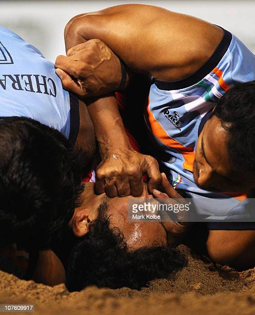 Meraj Sheiyk of Iran is tackled as he competes in the mens semi final match between India and Iran during Beach Kabaddi event at North Al Hail during...