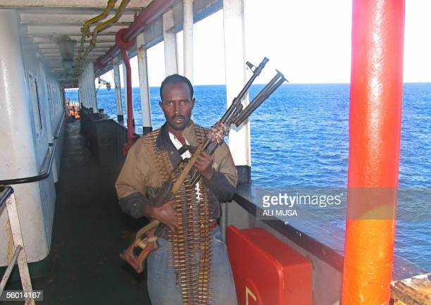 A Somali gunman carries a Russianmade long range machinegun in the porttown of Merca 26 October 2005 100 kilometers south of Mogadishu as he guards a...