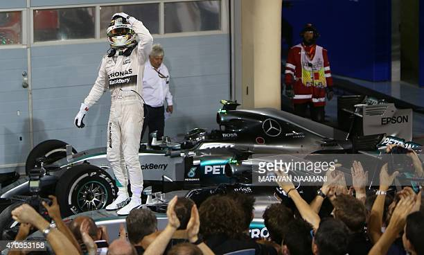 Mercedes AMG Petronas British driver Lewis Hamilton gestures towards members of his team as he celebrates on top of his car after winning the Formula...