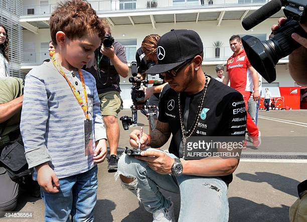 Mercedes AMG Petronas British driver Lewis Hamilton signs a toy car of a kid at the Paddock zone in Autodromo Hermanos Rodriguez in Mexico City on...