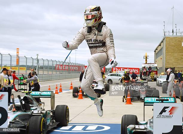 Mercedes AMG Petronas driver Lewis Hamilton of Britain leaps from his car as he celebrates winning the United States Formula One Grand Prix at the...