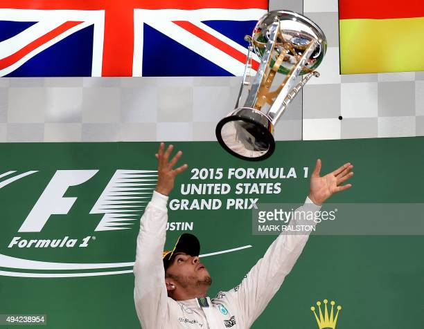 Mercedes AMG Petronas driver Lewis Hamilton of Britain throws his trophy on the podium as he celebrates winning the United States Formula One Grand...