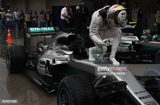 TOPSHOT Mercedes AMG Petronas F1 Team's British driver Lewis Hamilton celebrates after winning the Brazilian Grand Prix ahead of title rival and...