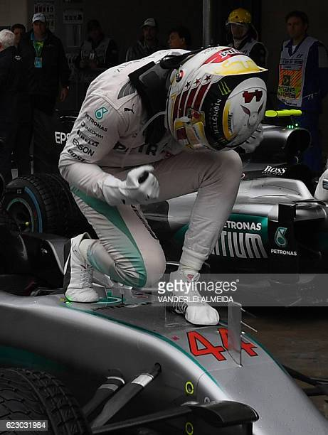 Mercedes AMG Petronas F1 Team's British driver Lewis Hamilton celebrates after winning the Brazilian Grand Prix ahead of title rival and Mercedes...