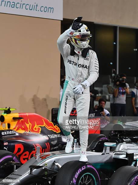Mercedes AMG Petronas F1 Team's British driver Lewis Hamilton celebrates after taking pole position in the qualifying session as part of the Abu...