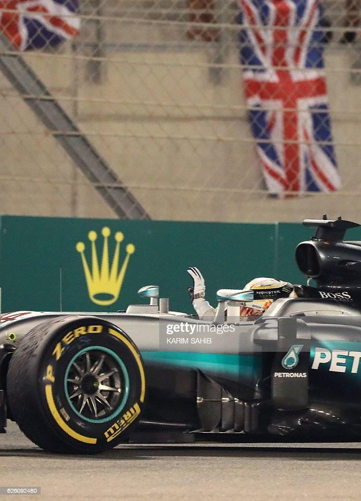 Mercedes AMG Petronas F1 Team's British driver Lewis Hamilton celebrates after winning the Abu Dhabi Formula One Grand Prix at the Yas Marina circuit on November 27, 2016. Nico Rosberg won his maiden Formula One world title by securing second place behind his Mercedes arch-rival Lewis Hamilton in the Abu Dhabi Grand Prix. / AFP / Karim Sahib