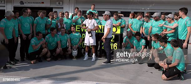Mercedes AMG Petronas F1 Team's British driver Lewis Hamilton and Mercedes AMG Petronas F1 Team's German driver Nico Rosberg celebrate with their...