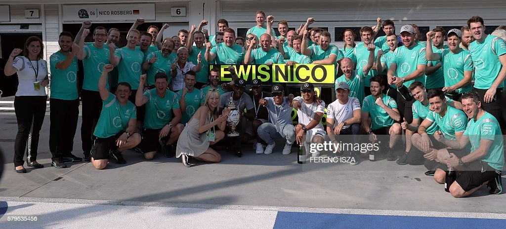 Mercedes AMG Petronas F1 Team's British driver Lewis Hamilton and Mercedes AMG Petronas F1 Team's German driver Nico Rosberg celebrate with their team after the Formula One Grand Prix of Hungary at Hungaroring on July 24, 2016 in Budapest, Hungary. / AFP / FERENC