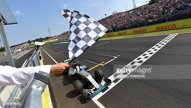 TOPSHOT Mercedes AMG Petronas F1 Team's British driver Lewis Hamilton crosses the finish line to win the Formula One Hungarian Grand Prix at the...