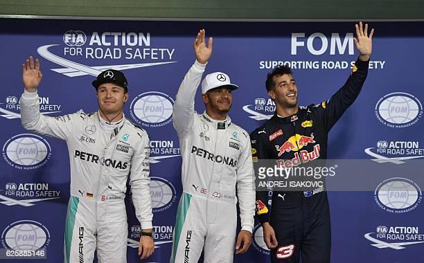Mercedes AMG Petronas F1 Team's British driver Lewis Hamilton , flanked by his German teammate Nico Rosberg and Infiniti Red Bull Racing's Australian...