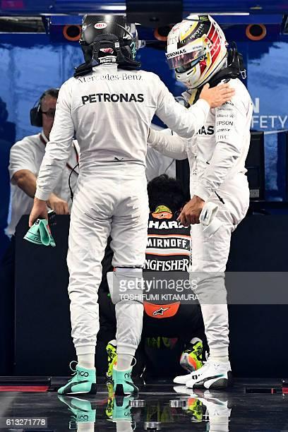 Mercedes AMG Petronas F1 Team's British driver Lewis Hamilton congratulates his teammate Mercedes AMG Petronas F1 Team's German driver Nico Rosberg...