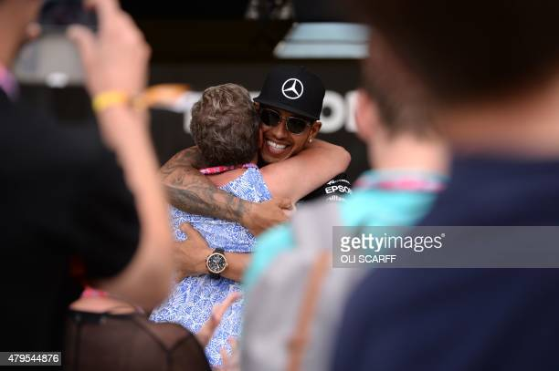 Mercedes AMG Petronas F1 Team's British driver Lewis Hamilton hugs his mother Carmen Larbalestier after winning the British Formula One Grand Prix at...