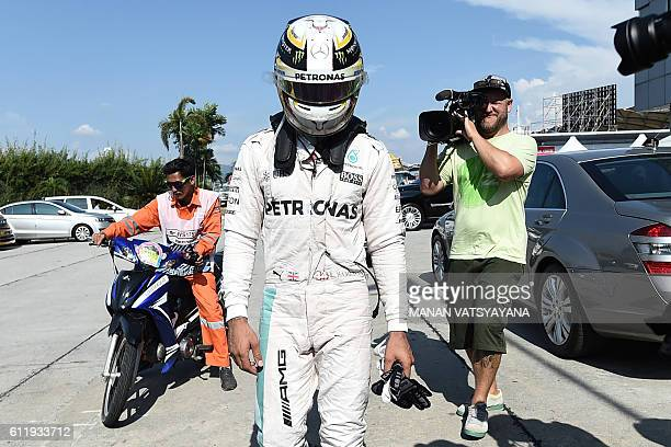 TOPSHOT Mercedes AMG Petronas F1 Team's British driver Lewis Hamilton is driven back to the pit after his car caught fire during the Formula One...