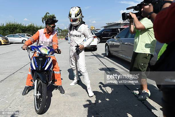 Mercedes AMG Petronas F1 Team's British driver Lewis Hamilton is driven back to the pit after his car caught fire during the Formula One Malaysian...