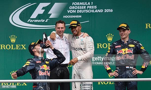 Mercedes AMG Petronas F1 Team's British driver Lewis Hamilton looks at second placed Red Bull Racing's Australian driver Daniel Ricciardo drinking...