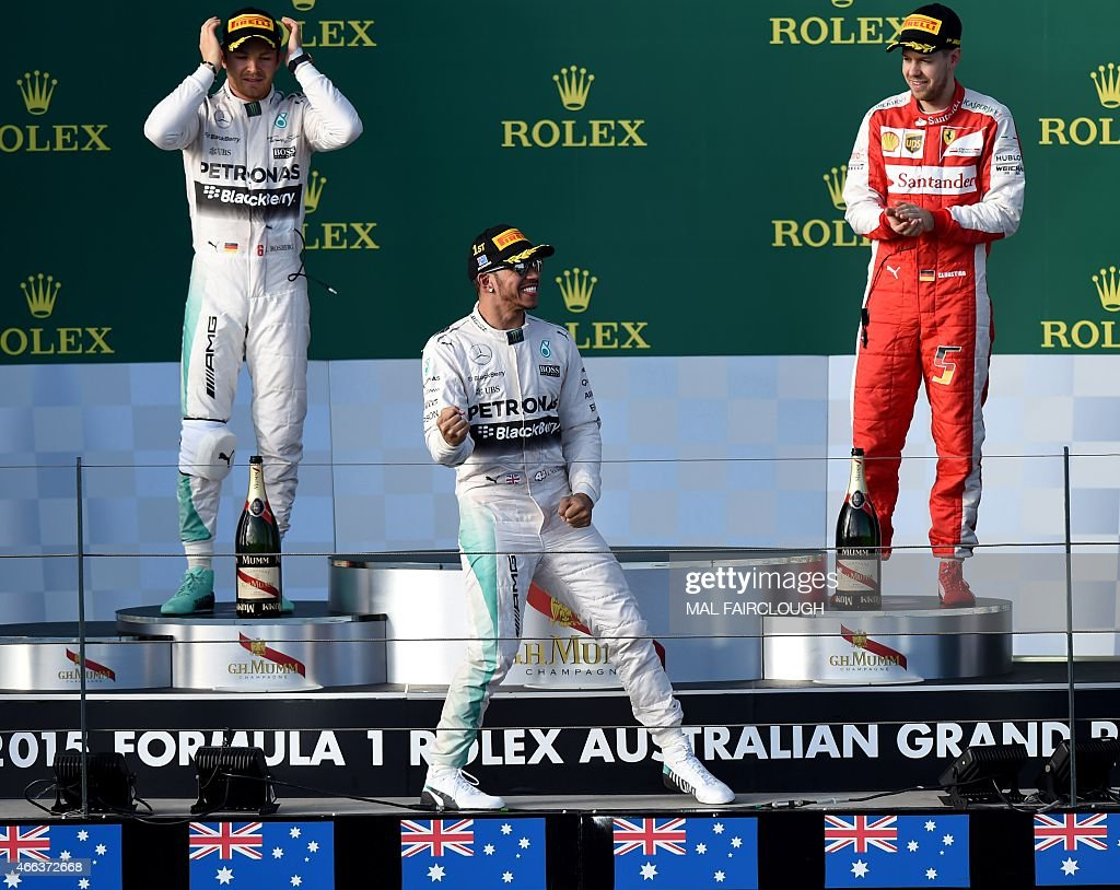 Mercedes AMG Petronas F1 Team's British driver Lewis Hamilton (C) celebrates on the podium in front of second placed teammate German driver Nico Rosberg (L) and third placed Ferrari's German driver Sebastian Vettel (R) after winning the Formula One Australian Grand Prix in Melbourne on March 15, 2015.