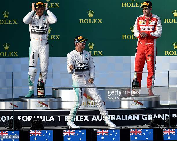 Mercedes AMG Petronas F1 Team's British driver Lewis Hamilton celebrates on the podium in front of second placed teammate German driver Nico Rosberg...