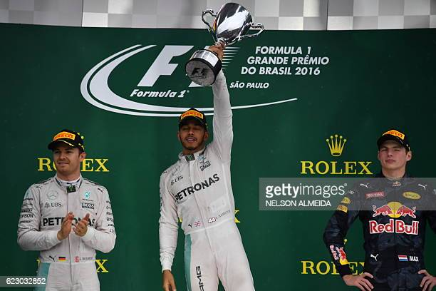 Mercedes AMG Petronas F1 Team's British driver Lewis Hamilton celebrates on the podium after winning the Brazilian Grand Prix ahead of title rival...