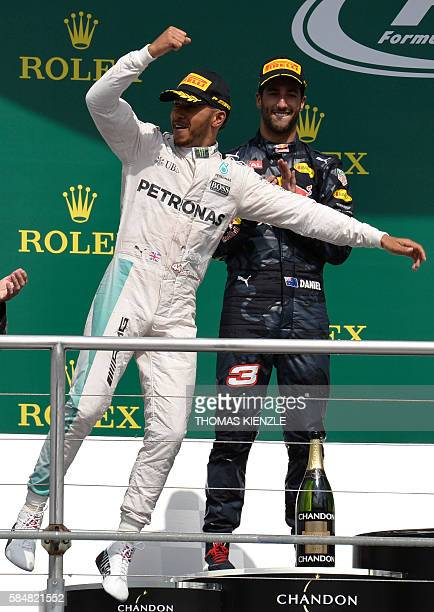 Mercedes AMG Petronas F1 Team's British driver Lewis Hamilton reacts after winning next to second placed Red Bull Racing's Australian driver Daniel...