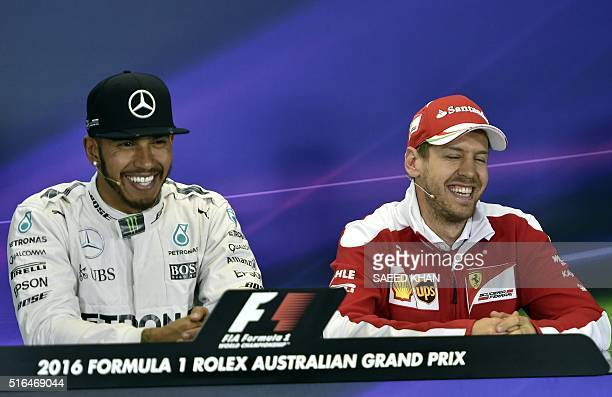 Mercedes AMG Petronas F1 Team's British driver Lewis Hamilton smiles with Ferrari's German driver Sebastian Vettel during a press conference after...
