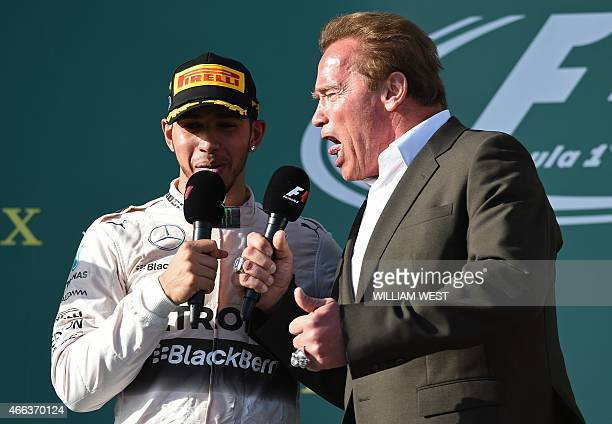 Mercedes AMG Petronas F1 Team's British driver Lewis Hamilton speaks on the podium next to Hollywood star Arnold Schwarzenegger after winning the...