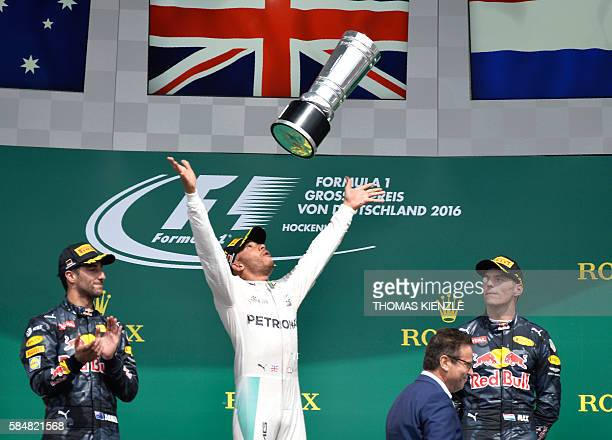 Mercedes AMG Petronas F1 Team's British driver Lewis Hamilton throws the trophy after winning next to second placed Red Bull Racing's Australian...