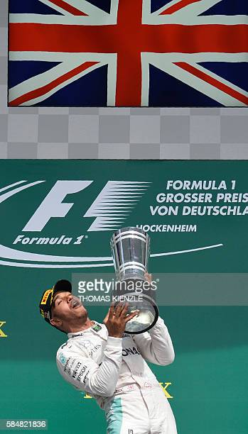 Mercedes AMG Petronas F1 Team's British driver Lewis Hamilton throws the trophy after winning at the Hockenheim circuit, southern Germany, on July...