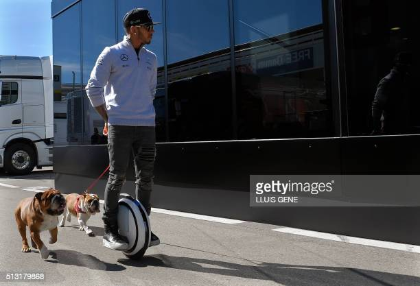 TOPSHOT Mercedes AMG Petronas F1 Team's British driver Lewis Hamilton uses a legway to walk his dogs at the paddock of the Circuit de Catalunya in...
