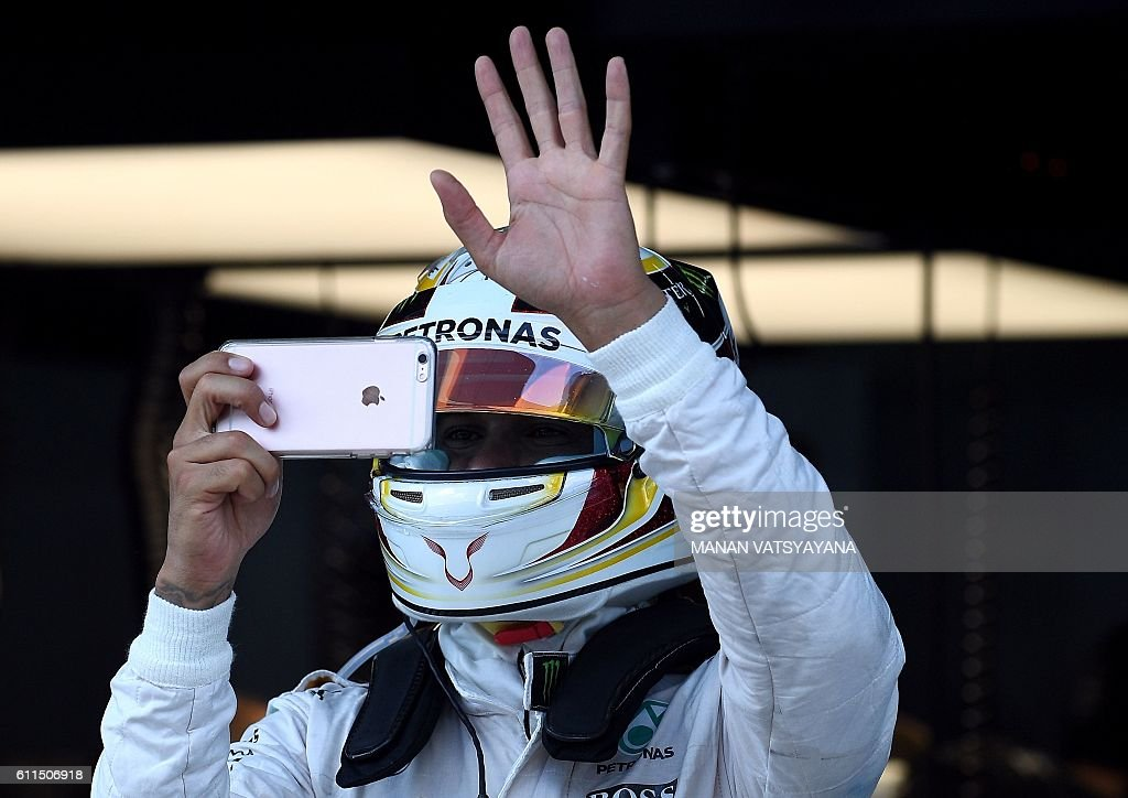 Mercedes AMG Petronas F1 Team's British driver Lewis Hamilton waves as he takes a picture with his phone during the second practice session of the Formula One Malaysian Grand Prix in Sepang on September 30, 2016. / AFP / MANAN