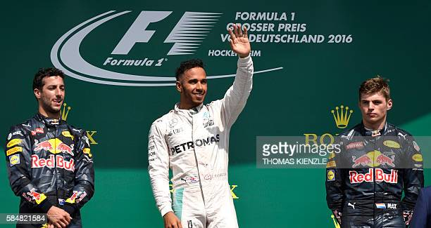 Mercedes AMG Petronas F1 Team's British driver Lewis Hamilton waves after winning next to second placed Red Bull Racing's Australian driver Daniel...