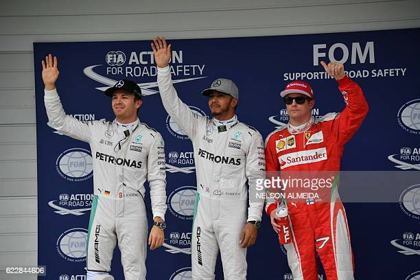 Mercedes AMG Petronas F1 Team's British driver Lewis Hamilton waves after grabbing pole position ahead of title rival and Mercedes teammate Nico...