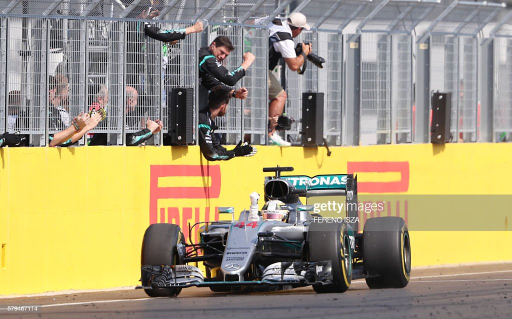 Mercedes AMG Petronas F1 Team's British driver Lewis Hamilton celebrates winning the Hungarian Formula One Grand Prix on July 24, 2016 at the Hungaroring circuit near Budapest. / AFP / FERENC