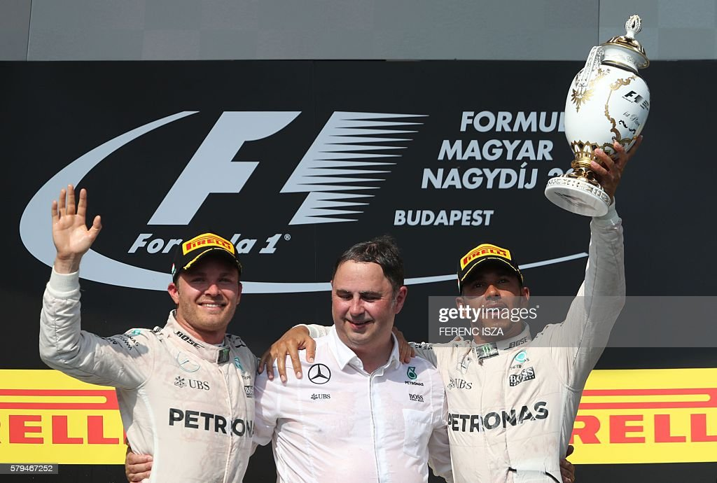 Mercedes AMG Petronas F1 Team's British driver Lewis Hamilton (R) celebrates winning the Hungarian Formula One Grand Prix next to Mercedes AMG Petronas F1 Team's German driver Nico Rosberg (L) and a team member on July 24, 2016 at the Hungaroring circuit near Budapest. / AFP / FERENC