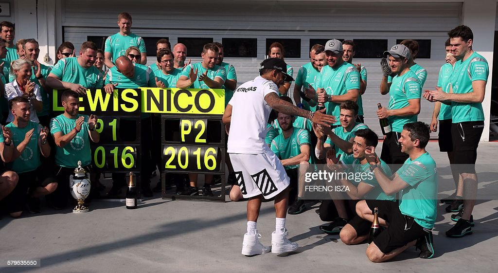 Mercedes AMG Petronas F1 Team's British driver Lewis Hamilton celebrates winning with his team after the Formula One Grand Prix of Hungary at Hungaroring on July 24, 2016 in Budapest, Hungary. / AFP / FERENC