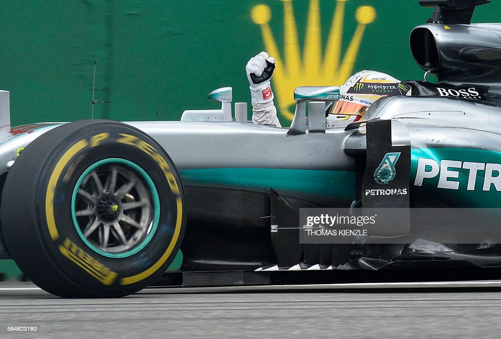 TOPSHOT - Mercedes AMG Petronas F1 Team's British driver Lewis Hamilton celebrates winning at the Hockenheim circuit, southern Germany, on July 31, 2016 during the Formula One Grand Prix of Germany. /