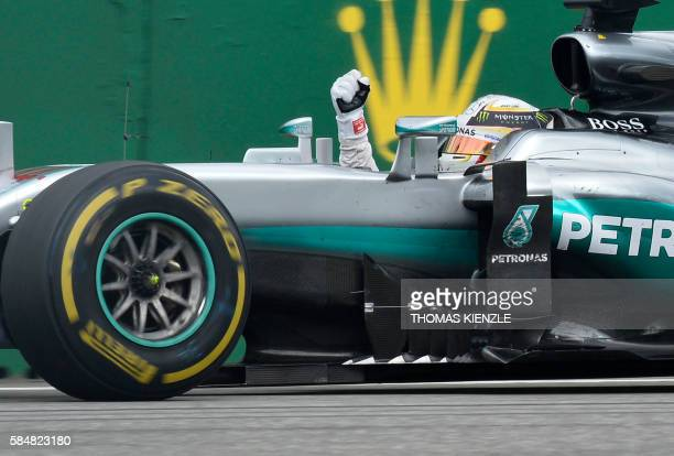 Mercedes AMG Petronas F1 Team's British driver Lewis Hamilton celebrates winning at the Hockenheim circuit, southern Germany, on July 31, 2016 during...
