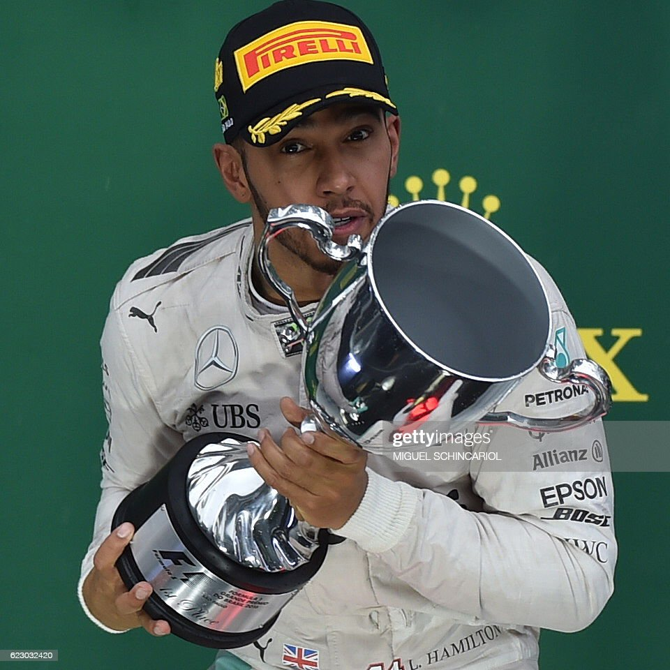TOPSHOT - Mercedes AMG Petronas F1 Team's British driver Lewis Hamilton celebrates with the trophy on the podium after winning the Brazilian Grand Prix ahead of title rival and Mercedes teammate Nico Rosberg at the Interlagos circuit in Sao Paulo, Brazil, on November 13, 2016. / AFP / Miguel SCHINCARIOL
