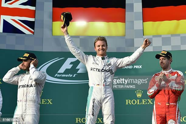 Mercedes AMG Petronas F1 Team's German driver Nico Rosberg celebrates on the podium next to Mercedes AMG Petronas F1 Team's British driver Lewis...