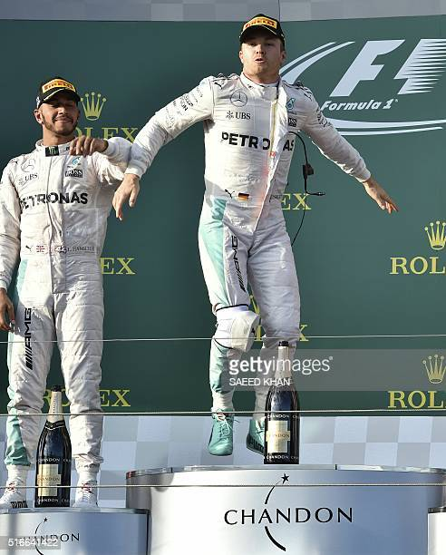 Mercedes AMG Petronas F1 Team's German driver Nico Rosberg celebrates with teammate British driver Lewis Hamilton on the podium at the end of the...