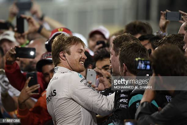 Mercedes AMG Petronas F1 Team's German driver Nico Rosberg celebrates with team mates and fans after winning the Bahrain Formula One Grand Prix at...