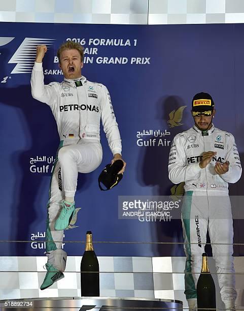 Mercedes AMG Petronas F1 Team's German driver Nico Rosberg celebrates on the podium after winning the Bahrain Formula One Grand Prix next to third...