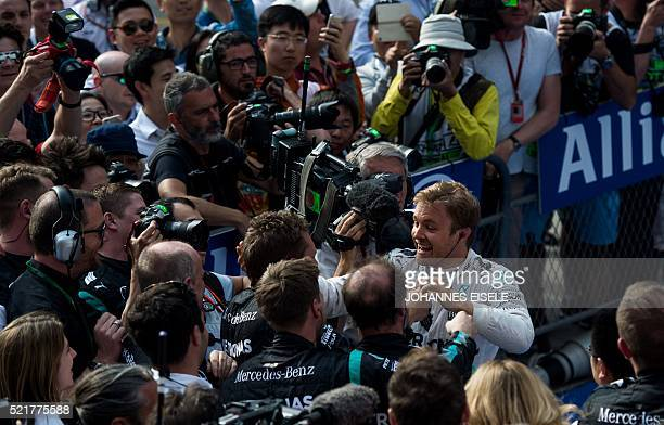 Mercedes AMG Petronas F1 Team's German driver Nico Rosberg celebrates with his team after winning the Formula One Chinese Grand Prix in Shanghai on...