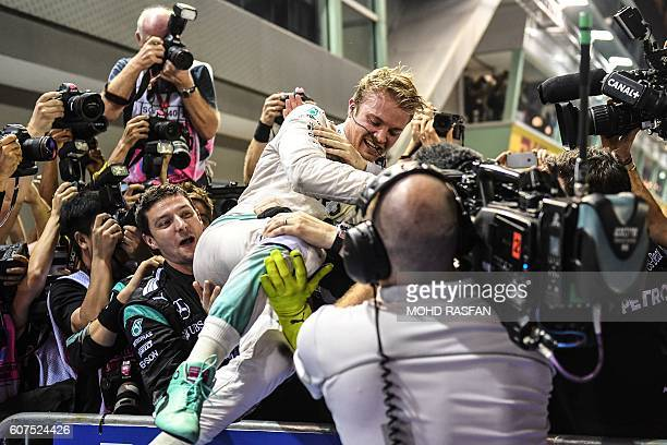 Mercedes AMG Petronas F1 Team's German driver Nico Rosberg celebrates with teammates after winning the Formula One Singapore Grand Prix in Singapore...